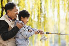 Stock Photo of Father and son fishing together at lake