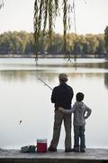 Grandfather and grandson fishing off of dock at lake - stock photo