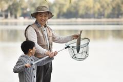Grandfather and grandson putting fish into net at lake Stock Photos