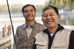 Senior friends portrait while fishing at a lake - stock photo