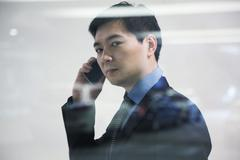 Businessman looking thorough window in parking garage, reflection of car Stock Photos