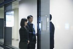 Three business people meeting and shaking hands, seen through glass wall - stock photo