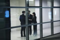 Stock Photo of Three business people meeting, seen through glass wall