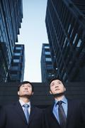 Two businessmen standing side by side outdoors, Beijing - stock photo