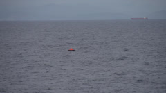 Mediterran sea, life raft floating alone, distant cargo freighter on the horizon Stock Footage
