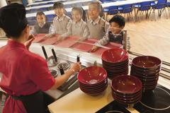 School cafeteria worker serves noodles to students Stock Photos