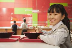 School girl eats noodles in school cafeteria - stock photo