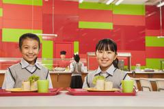 Two girls sitting in school cafeteria Stock Photos