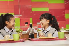 Two girls talking at lunch in school cafeteria Stock Photos