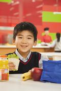 School boy portrait eating lunch in school cafeteria - stock photo
