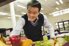 Teacher reaching for healthy food in school cafeteria - stock photo