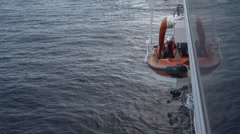 Mediterranean, rescue boat lowered onto ocean from ship - stock footage