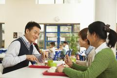 Teachers talking at lunch in school cafeteria Stock Photos
