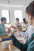 Coworkers eating and working in the cafeteria Stock Photos