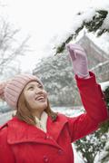 Young woman reaching for a branch in the snow - stock photo