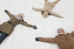 Family laying in snow making snow angels Stock Photos