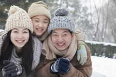 Family laying in snow for portrait Stock Photos