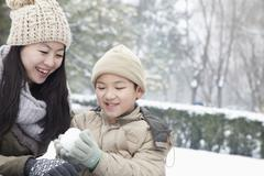 Mother helping son make snow ball - stock photo