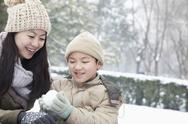 Stock Photo of Mother helping son make snow ball