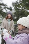 Girl Holding a snowman in a park with mother Stock Photos