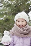 Girl Holding a snowman in a park - stock photo