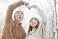 Young couple making heart shape in park in winter Stock Photos