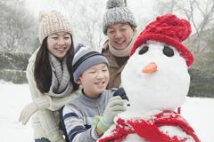 Family making snowman in a park in winter Stock Photos
