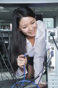Businesswoman Plugging Cord Into Back of Computer Stock Photos