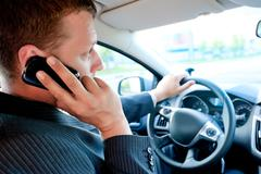 Male businessman talking on a cell phone while driving Stock Photos