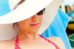 Portrait of a girl in a white hat with a wide brim on the beach Stock Photos
