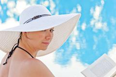 portrait of a beautiful woman sitting with a book by the pool - stock photo