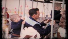 427 - boys get on merry-go-round at amusement park - vintage film home movie Stock Footage