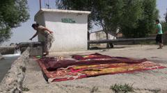 Woman prepares to clean carpets in Uzbek village Stock Footage