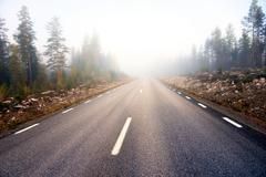 asphalt road on foggy morning - stock photo