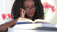 Black teenager calling a friend for homework help Stock Footage