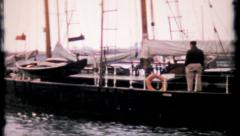 Large, classic sail boat moves slowly into dock, 337 vintage film home movie Stock Footage