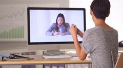 Chinese businesswoman talking to colleague via skype - stock footage