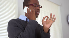 Black business man talking on mobile phone - stock footage