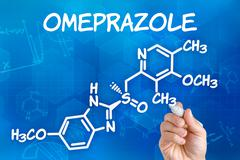 hand with pen drawing the chemical formula of omeprazole - stock photo
