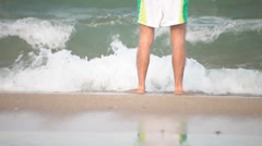 swimmer man wetting and conditioning feet in ocean. - stock footage