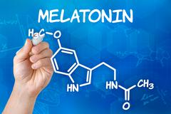 Hand with pen drawing the chemical formula of melatonin Stock Photos