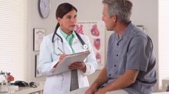 Doctor talking with her elderly patient - stock footage