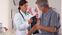 Woman doctor checking elderly man's blood pressure Stock Footage