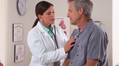 Stock Video Footage of Woman doctor listening to elderly patient's heartbeat