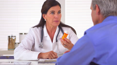 Woman doctor prescribing medication to elderly patient - stock footage