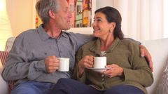 Happy senior couple talking on couch Stock Footage