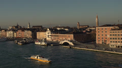Venice dolly shot passing city bridge and boats, wide shot, sunset Stock Footage
