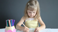 Pretty little girl drawing a picture with markers Stock Footage