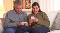 Mature wife showing pictures to her husband Stock Footage