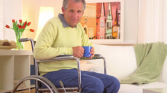 Stock Video Footage of Old man sitting in wheelchair with coffee